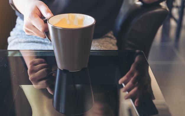 Chiuda sull'immagine di una donna che tiene le tazze da caffè in caffè