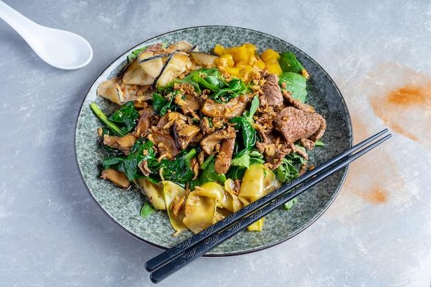 Chiuda sull'insalatiera tailandese panasiatica. cibo piatto disteso sulla superficie di pietra grigia. insalata tiepida di vitello, spinaci, funghi e spezie. copia spazio. banner, menu, foto poster