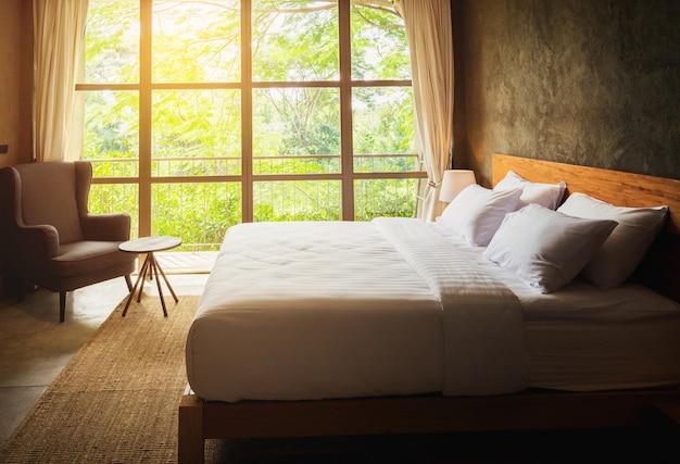 Chiuda sull'interno della serie della camera da letto con i cuscini e il fondo bianchi concreti della parete