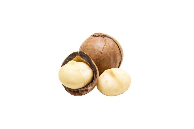 Chiuda sull'isolato delle noci di macadamia su bianco
