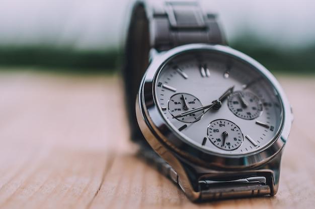 Chiuda sull'orologio dell'orologio della mano sulla tavola di legno