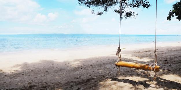 Chiuda sull'oscillazione di bambù che appende sotto il grande albero sulla spiaggia.