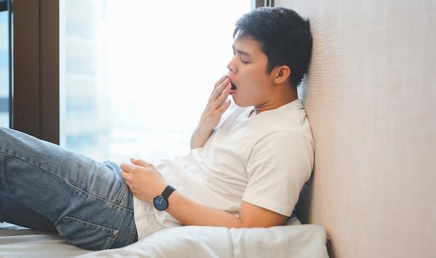 Chiuda sull'uomo asiatico assonnato e che sbadiglia alla camera da letto nel giorno di vacanza