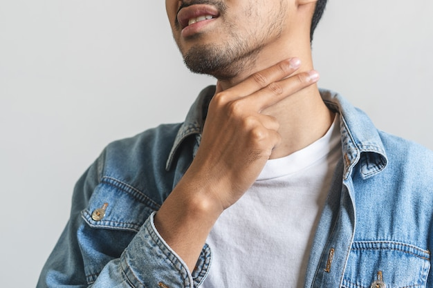 Chiuda sull'uomo asiatico che tocca il suo collo e che ha gola irritata.