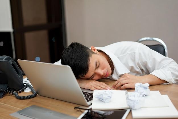 Chiuda sull'uomo asiatico impiegato che dorme e faccia un pisolino alla scrivania dopo il lavoro duro