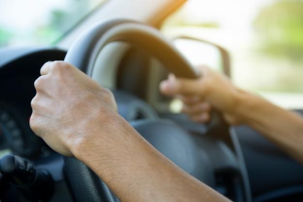 Chiuda sull'uomo che conduce l'automobile sulla via