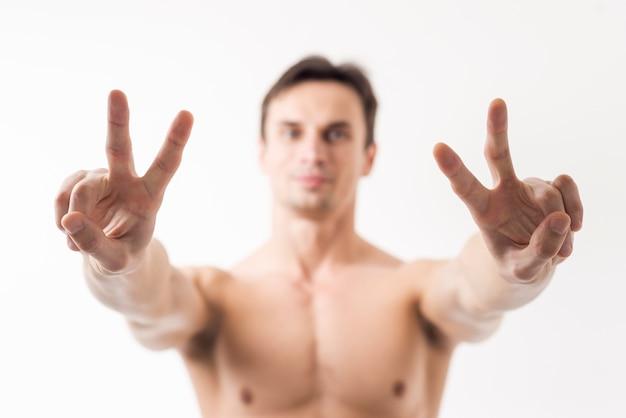 Chiuda sull'uomo che gesturing il segno di pace