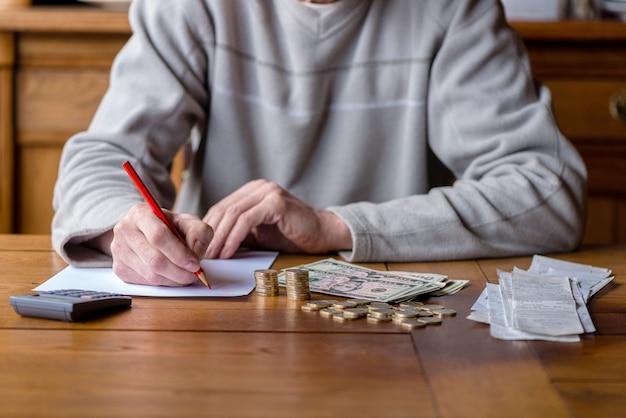 Chiuda sull'uomo con il conteggio del calcolatore, prendendo le note a casa, la mano è scrive in un taccuino. monete impilate sistemate a deesk. concetto di finanze di risparmio.
