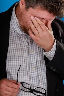 Chiuda sull'uomo esaurito che toglie gli occhiali che massaggiano il ponte del naso ritiene gli occhi affaticamento stra