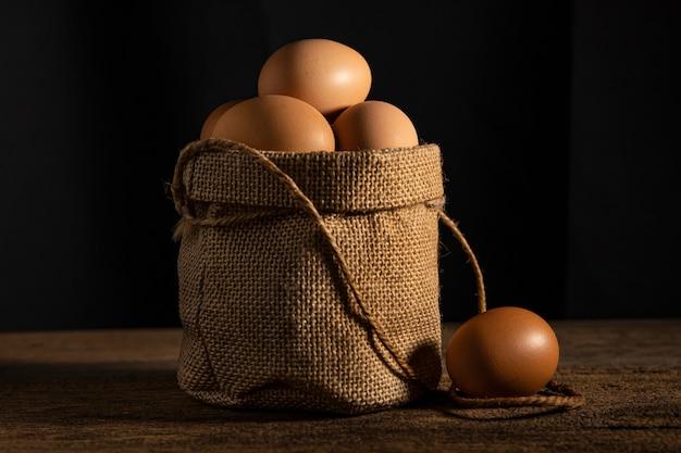 Chiuda sull'uovo in sacco del cotone sulla parete di legno della tavola