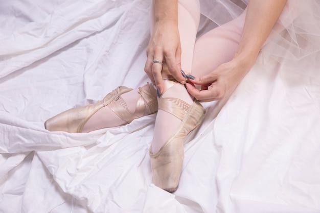 Chiuda sulla ballerina che lega le scarpe del pointe