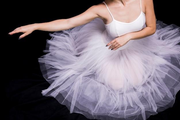 Chiuda sulla ballerina che si siede in vestito