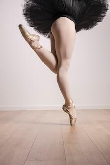 Chiuda sulla ballerina che sta in scarpe e tutu del pointe