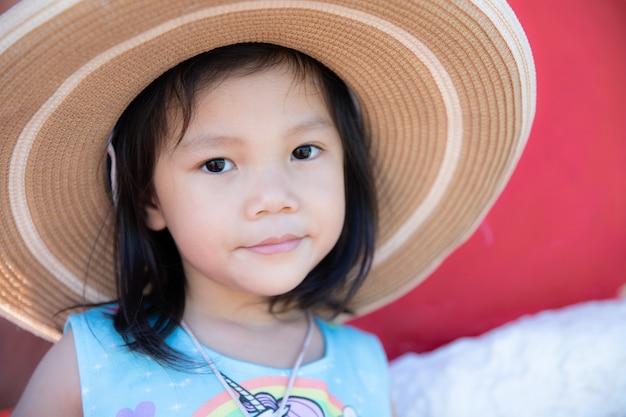 Chiuda sulla bambina sveglia indossa un grande cappello