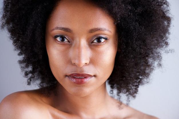 Chiuda sulla bella donna africana con capelli ricci e le spalle nude