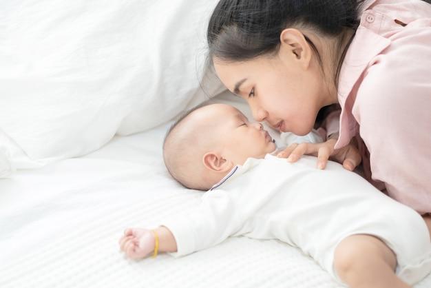 Chiuda sulla bella giovane madre asiatica che bacia il neonato sul letto. sanità e medicina. ragazza asiatica amore stile di vita.