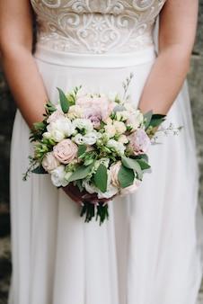 Chiuda sulla bella giovane sposa caucasica che tiene il suo mazzo moderno di nozze davanti lei il giorno delle nozze
