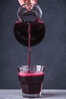 Chiuda sulla bevanda di frutta di versamento della mano in un vetro. ribes nero morse in un bicchiere.
