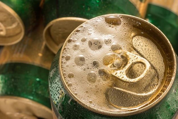 Chiuda sulla birra della latta fredda con la bolla della schiuma.