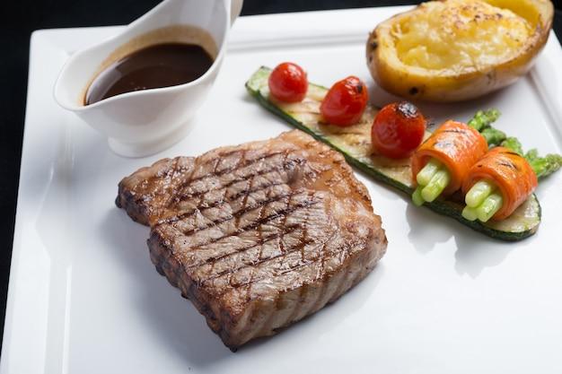 Chiuda sulla bistecca di manzo di hida con il pomodoro, la carota, il cetriolo e l'asparago arrostiti sul piatto bianco