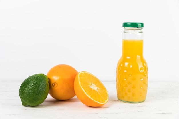 Chiuda sulla bottiglia del succo d'arancia sulla tavola