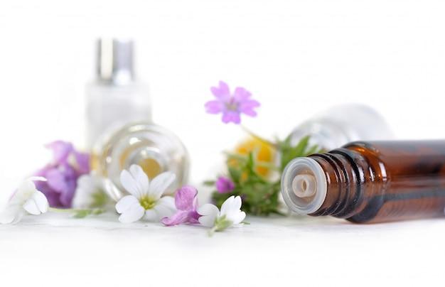Chiuda sulla bottiglia di olio essenziale rovesciato e sull'estremità bianca petali rosa dei fiori su bianco