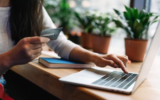 Chiuda sulla carta di credito della tenuta della mano della donna, comperante online