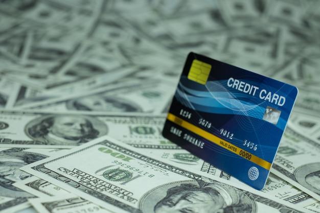 Chiuda sulla carta di credito isolata alla pila di banconote dei soldi una parete da 100 usd