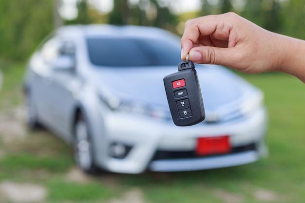 Chiuda sulla chiave della tenuta della mano della donna di nuova automobile