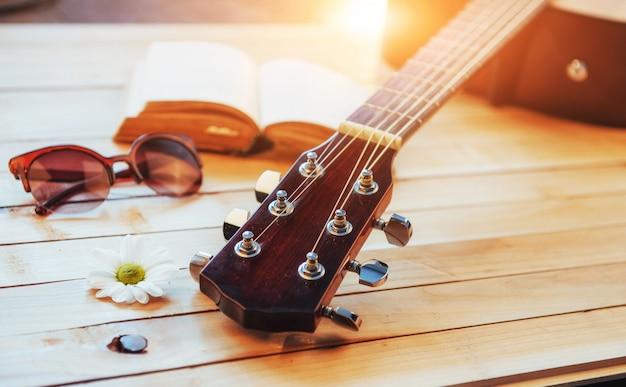 Chiuda sulla chitarra classica acustica del collo su un fondo di legno leggero