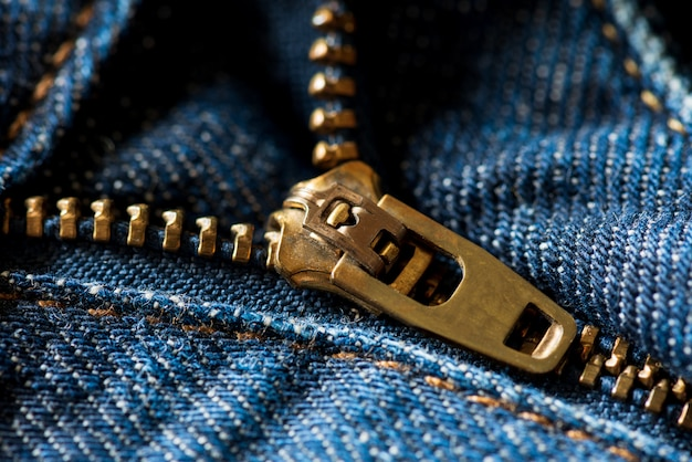 Chiuda sulla chiusura lampo delle blue jeans