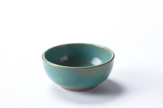 Chiuda sulla ciotola di ceramica isolata sul tiro bianco della priorità bassa nello studio con spazio per la copia.