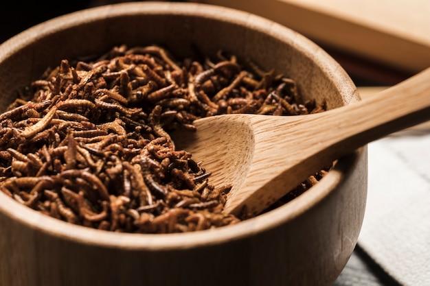 Chiuda sulla ciotola di legno in pieno di larve