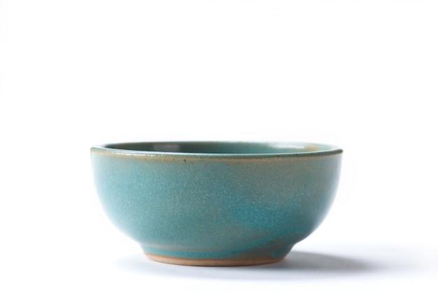 Chiuda sulla ciotola verde ceramica isolata sul tiro bianco del fondo nello studio con spazio per la copia.