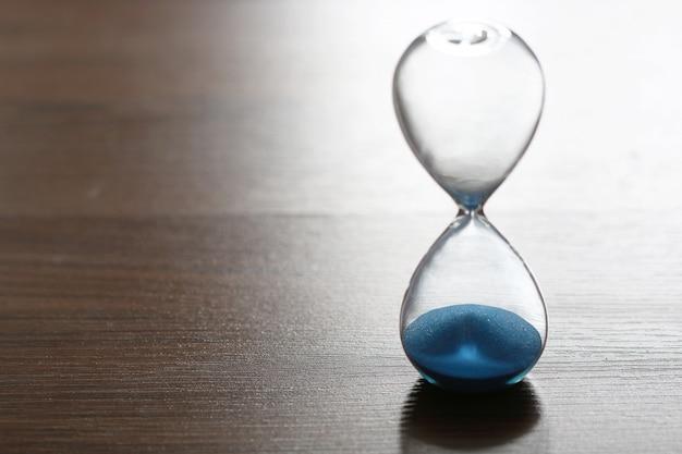 Chiuda sulla clessidra sul pavimento di legno per il concetto di tempo