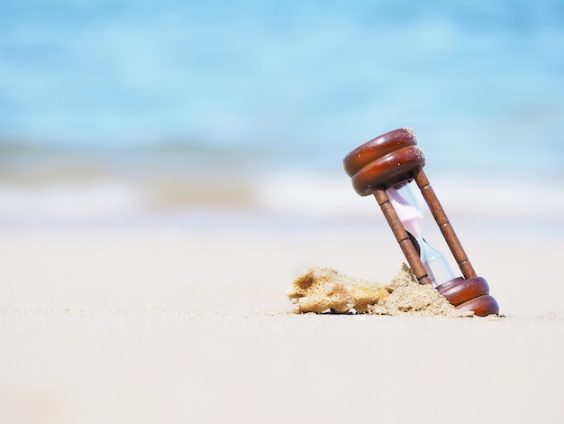Chiuda sulla clessidra sulla spiaggia di estate.
