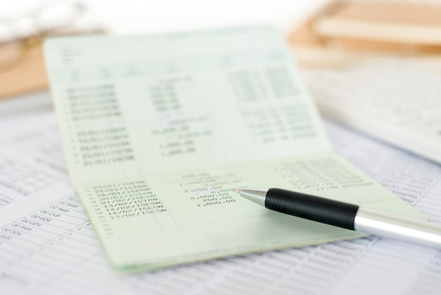 Chiuda sulla dichiarazione di conto di risparmio del libretto con una penna