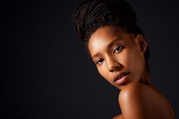 Chiuda sulla donna abbastanza africana con le spalle nude che esamina la macchina fotografica