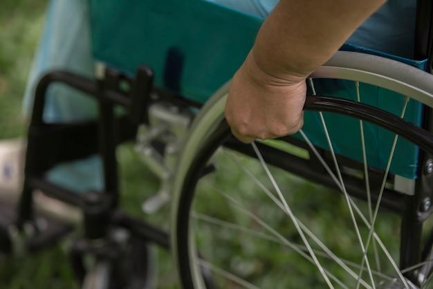 Chiuda sulla donna anziana sola che si siede sulla sedia a rotelle al giardino in ospedale