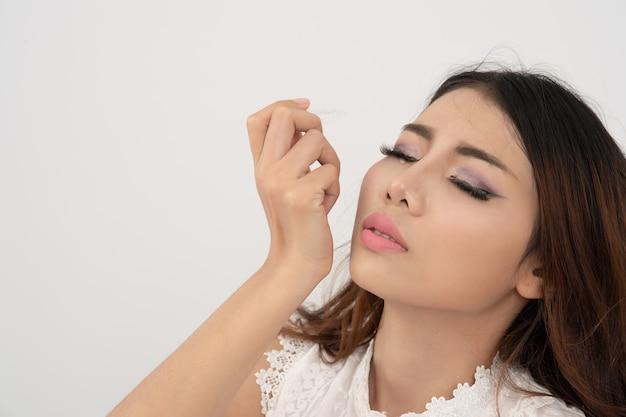 Chiuda sulla donna asiatica che usando il collirio, lubrificante cadente dell'occhio della donna tailandese per trattare l'occhio asciutto o l'allergia; giovane femmina che ottiene la medicina nell'occhio su fondo bianco.