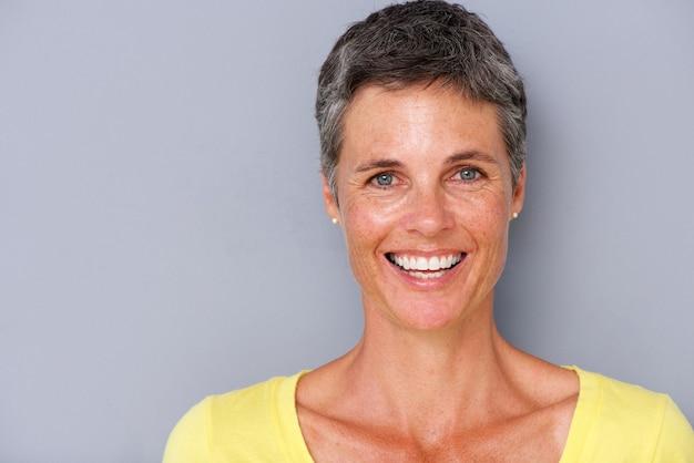 Chiuda sulla donna attraente di medio evo che sorride contro il fondo grigio