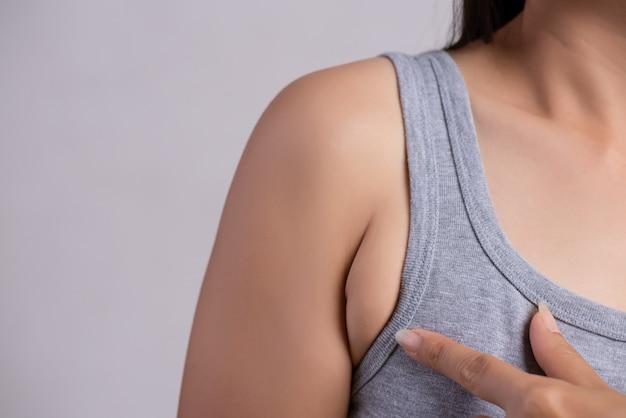 Chiuda sulla donna che indica la sua pelle ascellare. concetto di pelle grassa ascella problema.