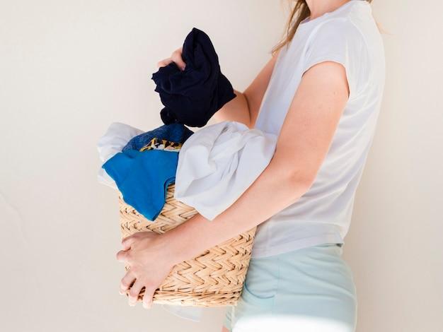 Chiuda sulla donna che tiene il canestro di lavanderia pieno