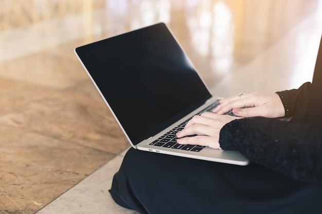 Chiuda sulla donna delle mani che si siede facendo uso del lavoro al computer portatile, concetto di affari.