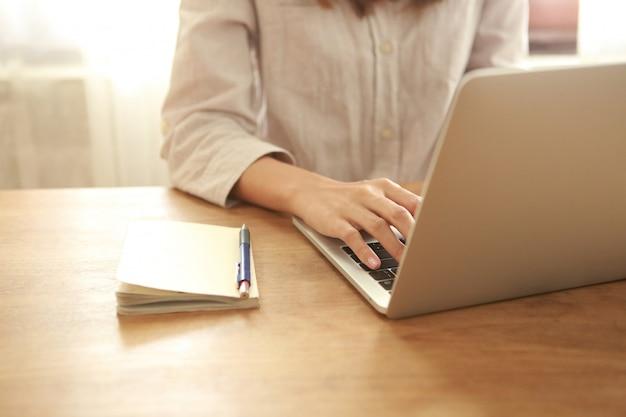 Chiuda sulla donna di affari che per mezzo del computer portatile sullo scrittorio di legno