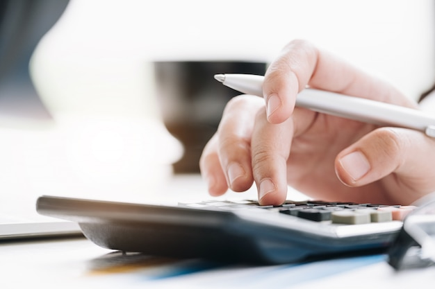 Chiuda sulla donna di affari che utilizza il calcolatore ed il computer portatile per finanzi la matematica sullo scrittorio di legno nell'ufficio