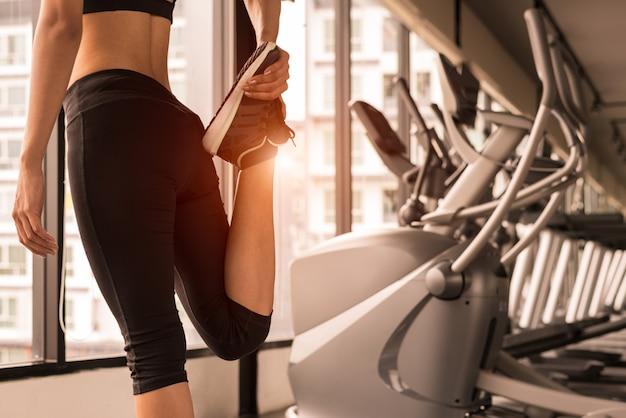 Chiuda sulla donna di bellezza che allunga le gambe nel centro della palestra di forma fisica di allenamento