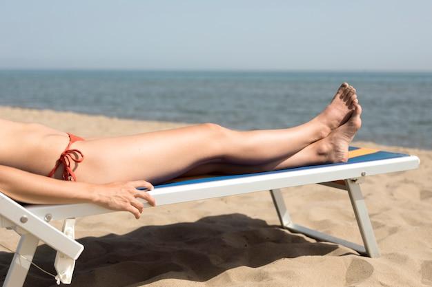 Chiuda sulla donna di vista laterale sulla sedia di spiaggia che prende il sole
