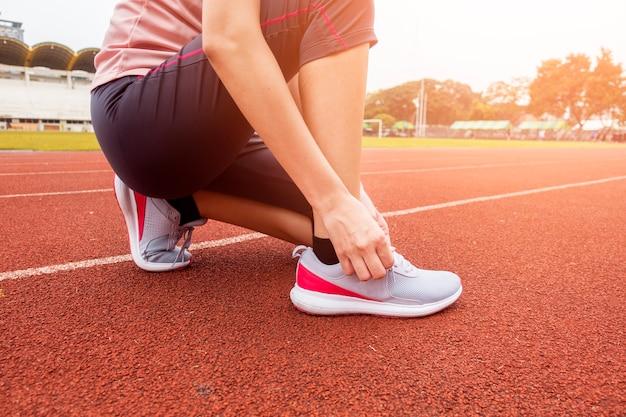Chiuda sulla donna è scarpa legare nel campo sportivo