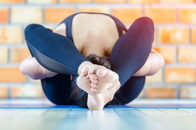 Chiuda sulla donna forte dell'apprendista asiatico che pratica la posa difficile di yoga in un fondo concreto